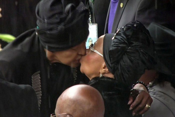 Winnie Mandela kisses Graca Mandela at one of the events celebrating the life of Nelson Mandela