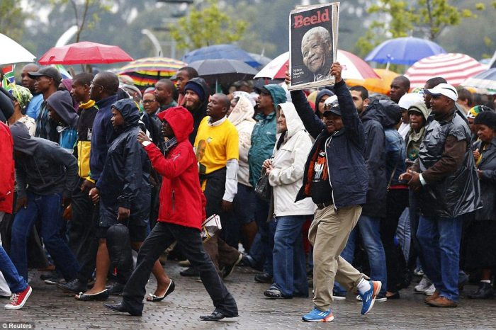 Getting ready: Crowds have been piling up around the First National Bank stadium where Mandela's memorial service will be held on Tuesday