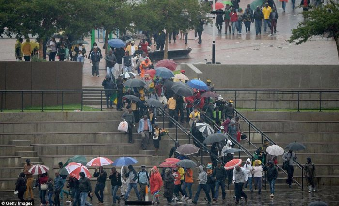 Queues: Members of the public clutching umbrellas to protect against the rain file in to the stadium in Soweto