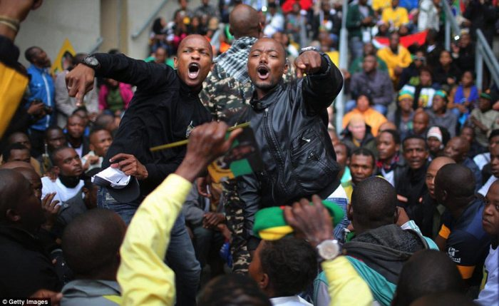 Festive: Men singing in the queue for the ceremony at South Africa's largest football stadium