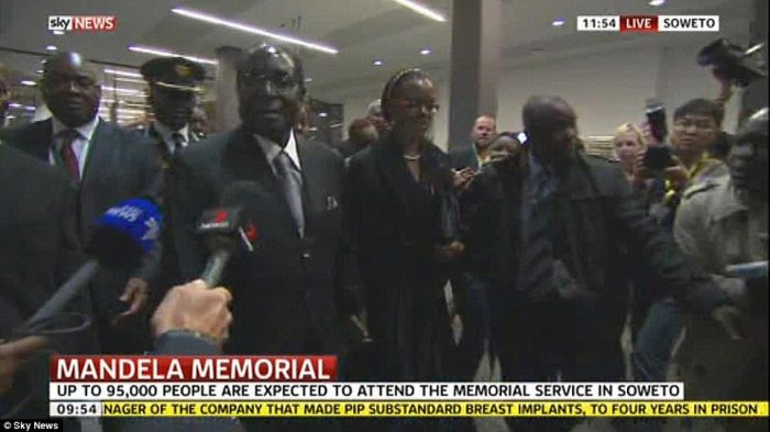 Controversial: Reviled Zimbabwean President Robert Mugabe is questioned by reporters as he makes his way into the stadium