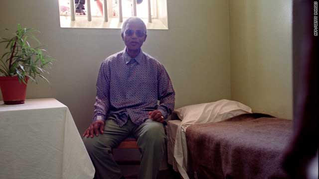 """The South African government periodically made conditional offers of freedom to Mandela, all of which he refused. Here, Mandela can be seen inside his old cell during a visit to the Robben Island prison on 10 February 1995. """"His answer was I want to be the last political prisoner in the country that is released,"""" says George Bizos, who advised Mandela during the legal fight against apartheid. """"They did not understand the integrity and humanity of people like Mandela."""""""