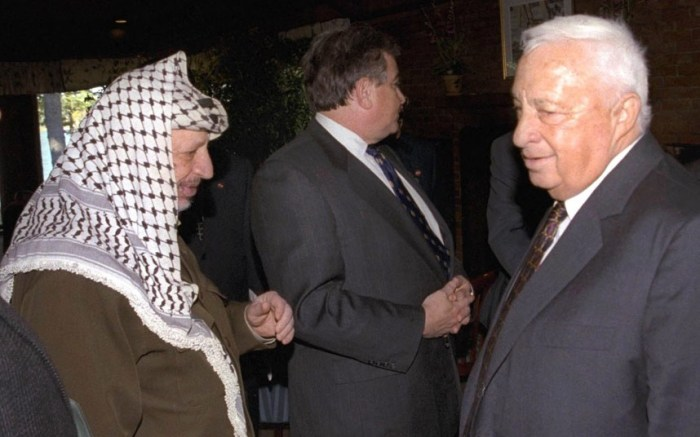 In October 1998 Ariel Sharon (right) stands near but does not look at, or shake hands with, Palestinian leader Yasser Arafat at Wye Plantation, Maryland. Before becoming a candidate, Sharon proudly boasted he had never shaken hands with Arafat, and called the Palestinian leader a murderer and a liar in an interview with the New Yorker magazine. (Picture: AP)