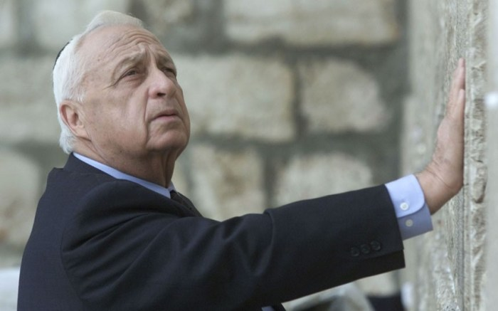 Ariel Sharon looks up as his touches Judaism holiest site the Western Wall in Jerusalem (Picture: AP)