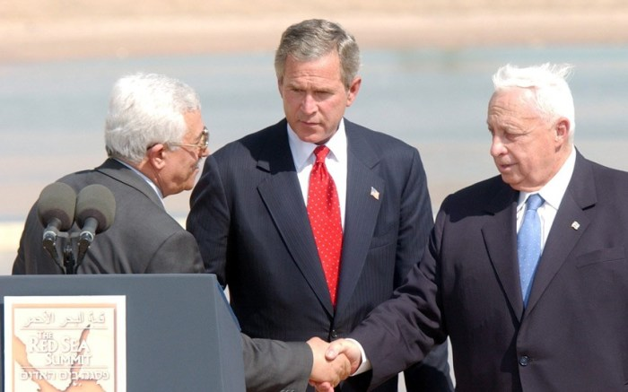 Palestinian Prime Minister Mahmoud Abbas (left) shakes hands with Ariel Sharon while being watched by U.S. President George W. Bush after their closing statements to the media following their summit meeting at the Royal Palace in Aqaba, Jordan in 2003 (Picture: HUSSEIN MALLA/EPA)