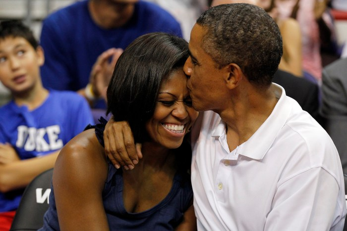 President Barack Obama kisses the head of first lady Michelle Obama after kissing her for 'Kiss Cam' while attending the Olympic men's exhibition basketball game between Team USA and Brazil, Monday, July 16, 2012, in Washington. Team USA won 80-69. (Photo Credit: AP Photo/Alex Brandon)