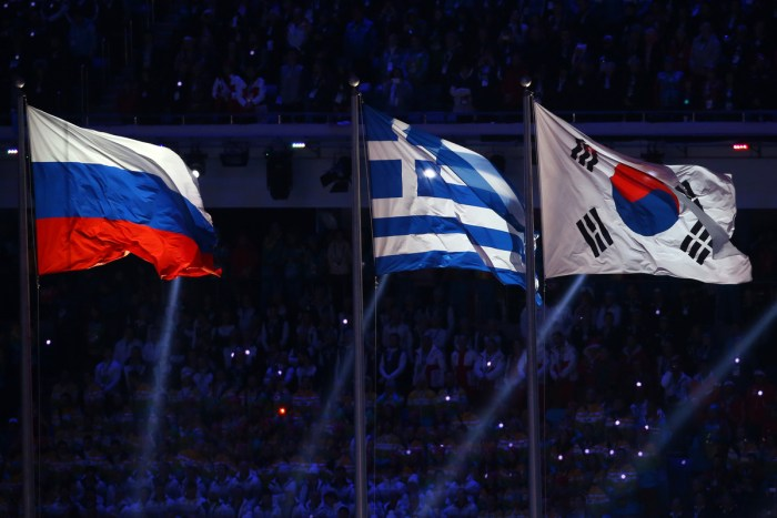 SOCHI, RUSSIA - FEBRUARY 23: The national flag of South Korea (R) is raised next to the flags of Russia (L) and Greece during the 2014 Sochi Winter Olympics Closing Ceremony at Fisht Olympic Stadium on February 23, 2014 in Sochi, Russia. (Photo by Doug Pensinger/Getty Images)