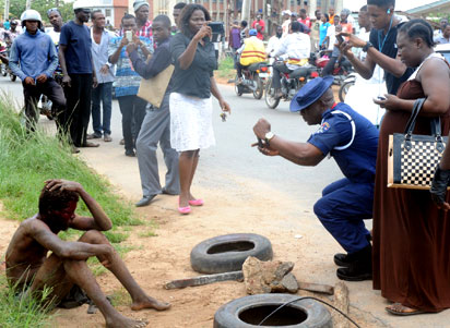 By standers, including a Civil Defence officer take snaps of the alleged ritualist at Ring Road, Ibadan
