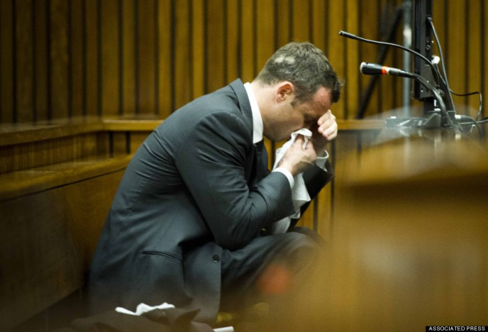 Oscar Pistorius, puts a handkerchief to his face while listening to cross questioning about the events surrounding the shooting death of his girlfriend Reeva Steenkamp, during his trial in Pretoria, South Africa, Friday, March 7, 2014. Pistorius is charged with murder for the shooting death of  Steenkamp, on Valentines Day in 2013. (Photo Credit: AP/Theana Breugem, Pool)