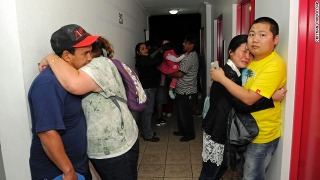 People embrace on the upper floor of an apartment building in Iquique, Chile, where they gathered after an 8.2-magnitude earthquake triggered a tsunami off the town's coast on Tuesday, April 1. (Photo Credit: CNN)