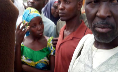 One of the lucky abducted students in Chibok who was later rescued and being handed over by her parents at school premises on Monday. (Photo Credit: Vanguard/Ndahi Maiduguri)