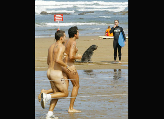 PHOTO: A surfer watches naked runners taking part in the Patxi Ros nudist cross-country race, 15 September 2007 on the beach by Sopelana, Spain. (Photo Credit: RAFA RIVAS/AFP/Getty Images)