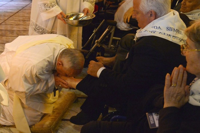 Pope Francis (L) kisses the foot of a man as he performs the traditional Washing of the feet during a visit at a center for disabled people as part of Holy Thursday (Maundy Thursday) as part of the Holy Week on April 17, 2014 in Rome. AFP PHOTO / ALBERTO PIZZOLI (Photo Credit: ALBERTO PIZZOLI/AFP/Getty Images)