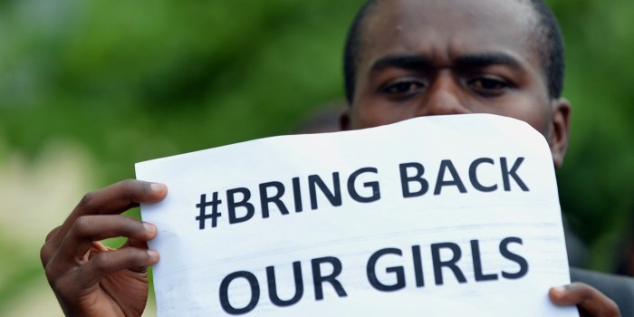 A participant at the World Conference on Youth 2014, hosted by Sri Lanka, poses for a photograph while holding a placard during a protest to demand the return of hundreds of school girls abducted by the Boko Haram separatist group in Colombo on May 9, 2014. (Photo Credit: Ishara S.KODIKARA/AFP/Getty Images)