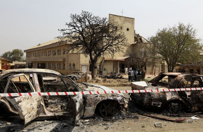 A security barrier marks the scene of a car bomb explosion at St. Theresa Catholic Church (background) at Madalla, Suleja, just outside Nigeria's capital Abuja, December 25, 2011. Islamist militant group Boko Haram said it planted bombs that exploded on Christmas Day at churches in Nigeria, one of which killed at least 27 people on the outskirts of the capital. (Photo Credit: REUTERS/Afolabi Sotunde)