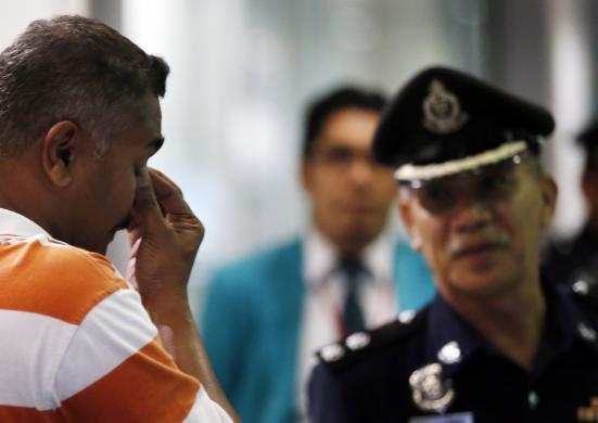 A man who said he believes he had a relative on Malaysia Airlines flight MH17 reacts in front of a policeman while waiting for more information about the crashed plane at Kuala Lumpur International Airport in Sepang July 18, 2014. [Photo Credit: REUTERS/Olivia Harris]