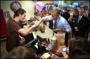 President Obama fist bumps a gay cashier in Texas [Photo Credit: Doug Mills/New York Times]