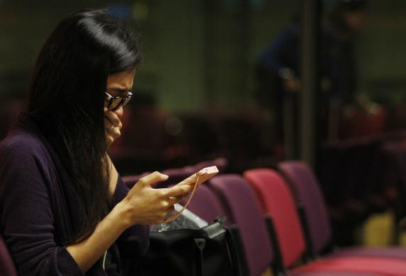 A Malaysian woman who had a relative on board the Malaysian Airlines MH17 reacts to messages on her mobile phone as she waits to travel to Kuala Lumpur International Airport from Singapore's Changi Airport July 18, 2014. (Photo Credit: REUTERS/Edgar Su)