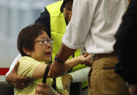 Malaysian Siti Dina weeps after seeing her daughter's name on the list of passengers on board Malaysia Airlines MH17 at the Kuala Lumpur International Airport in Sepang July 18, 2014. (Photo Credit: REUTERS/Edgar Su)