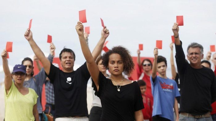 Protesters hold up red cards to signify their opposition to the 2014 World Cup. Source: Mashable