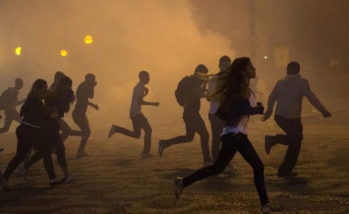 People flee through clouds of tear gas in a June 20th protest. Source: Mashable