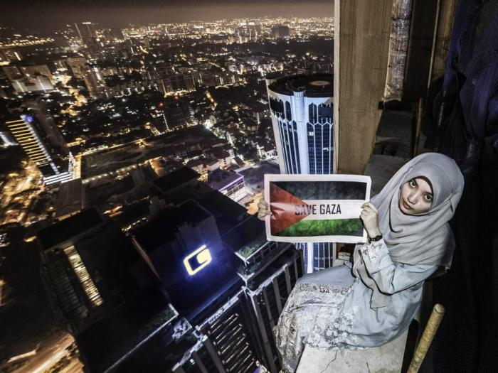 Fatin Ilani poses with a 'Save Gaza' posted at the top of the 53-floor IB Tower building in Kuala Lumpur. [Photo Credit: Cater News Agency]