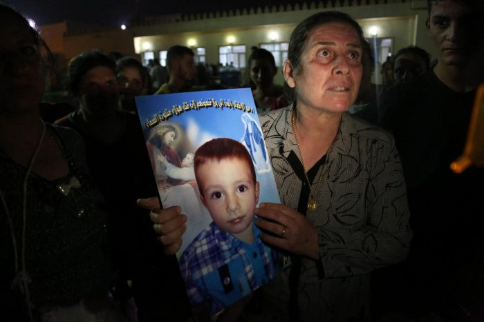 A displaced Iraqi Christian woman holds a picture of her four-year-old relative, David, who was killed by militants. (Photo Credit: US News)