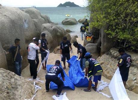 Thai officers work near the bodies of two British tourists Monday, Sept. 15, 2014 on a beach in Surat Thani province, southern Thailand. Their bodies were discovered early Monday on a beach on Koh Tao, a small island known for its diving sites and serene beaches, police said. (Photo Credit: AP Photo/Daily News)