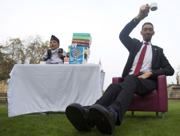 Chandra Bahadur Dangi, from Nepal, (L) the shortest adult to have ever been verified by Guinness World Records, poses for pictures with the world's tallest man Sultan Kosen from Turkey, during a photocall in London on November 13, 2014, to mark Guinness World Records Day. Chandra Dangi, measures a tiny 21.5in (0.54m) the same height as six stacked cans of beans. Sultan Kosen measures 8 ft 3in (2.51m). (Photo Credit: Andrew Cowie/AFP/Getty Images)