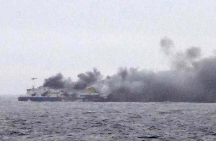 In this photo taken from a nearby ship, smoke rises from the Italian-flagged Norman Atlantic after it caught fire in the Adriatic Sea, Sunday, Dec. 28, 2014. The ferry carrying hundreds of passengers caught fire off the Greek island of Corfu early Sunday, trapping passengers on the top decks as gale-force winds and choppy seas hampered the evacuation. (Photo Credit: SKAI TV Station)