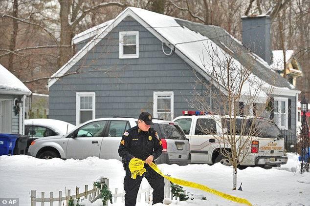 A police officer holds a roll of barrier tape outside the house in Closter, New Jersey. where a couple, Mr and Mrs Michael Tabacchi was found dead in a possible murder-suicide. (Photo Credit: Facebook)