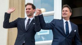 Luxembourg's Prime Minister Xavier Bettel, right, holds up the hand of his partner Gauthier Destenay, with a wedding band on his finger, as they leave the town hall after their marriage in Luxembourg, on Friday, May 15, 2015. The marriage comes one year after the parliament approved legislation to turn Luxembourg into an increasing number of countries allowing same-sex marriages. Bettel and Destenay have been civil partners since 2010. (AP Photo / Charles Caratini)