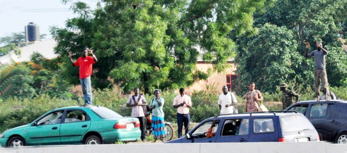 Soldiers force traffic offenders to stand on top of their vehicles in Abuja on June 3, 2015(Photo Credit: The Scoop)