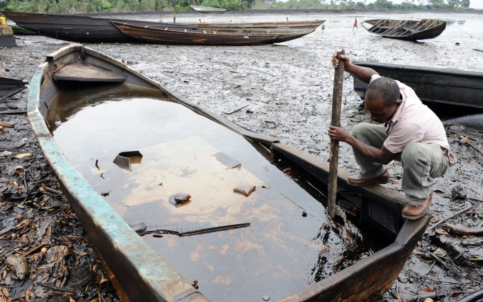 Niger Delta: An indigene of Bodo, Ogoniland region in Rivers State, tries to separate with a stick the crude oil from water in a boat at the Bodo waterways polluted by oil spills attributed to Shell equipment failure August 11, 2011 | AFP/Pius Ekpei
