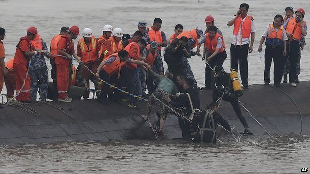Rescuers standing on the  capsized ship's hull pulling out a 65 year old woman (Credit: BBC/AFP)