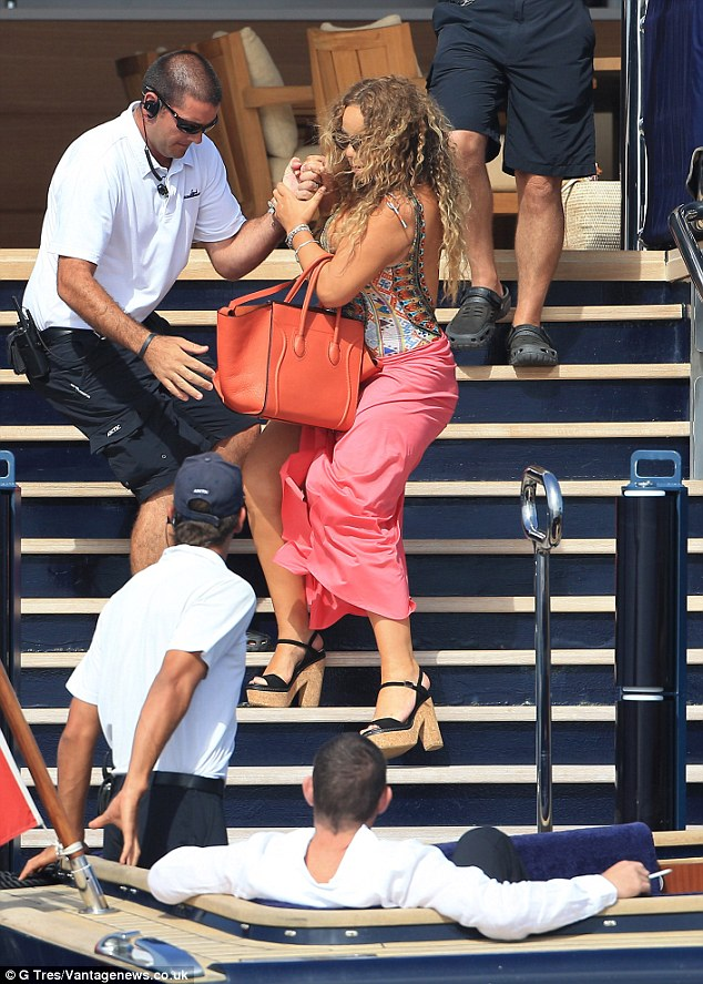 Covering up: A pink sarong was tied loosely around her waist and an orange handbag looped over one arm
