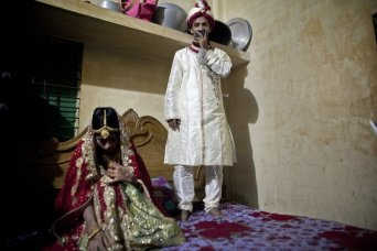32-year-old Mohammad Hasamur Rahman stands on a bed next to his new bride, 15-year-old Nasoin Akhter, Aug. 20, 2015 in Manikganj, Bangladesh. (Photo Credit: Allison Joyce/Getty Images)