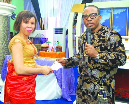 Pastor Chris Ekeh (Right) presenting a cheque to Miss Ngozi Mberekpe (Left) , a former inmate of the Kirikiri Prison | Vanguard