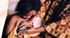 "YAOUNDE, CAMEROON - JUNE 22: A video grab of a woman ""ironing' her daughters breasts in an effort to stop them growing. A group of young mums are speaking out about a terrible painful ritual being carried out on young girls in Cameroon. 'Breast Ironing' is done on girls as young as six, and involves their chests being pressed with burning rocks and blunted knives. The ""traditional"" practice aims to stop breasts from growing, but leaves the girls crippled, scarred and in agony. Parents believe that if girls develop too young, they will become promiscuous and fall pregnant, or get raped by men. (Photo by Barcroft Media / Getty Images)"