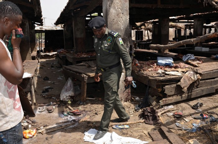 A Nigerian policeman inspects the site of a suicide attack at a busy cattle market in the northeastern Nigerian city of Maiduguri on June 2, 2015. | AFP/Stringer