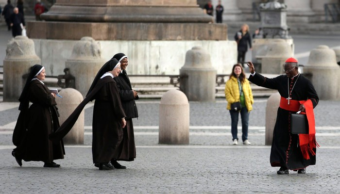 Cardinal Francis Arinze of Nigeria waves at nuns as he arrives for a meeting at the Synod Hall at the Vatican, March 8, 2013. | Reuters/Max Rossi