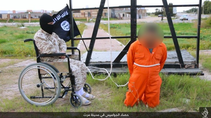 """ISIS Propaganda: The wheelchair-bound militant sits next to an alleged """"spy"""" before he is lifted up by a rope and crucified. 