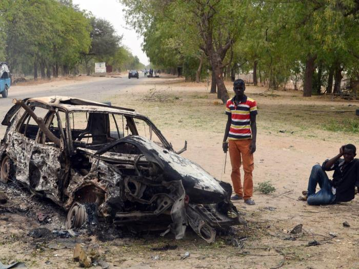 Two men next to a burnt out car in Maiduguri after a bomb attack by Boko Haram | Getty Images