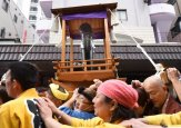Believers of the Wakamiya Hachimangu Shrine carry a portable shrine bearing a phalluse during the Kanamara Festival in Kawasaki, a suburb of Tokyo on Sunday, April 3, 2016.