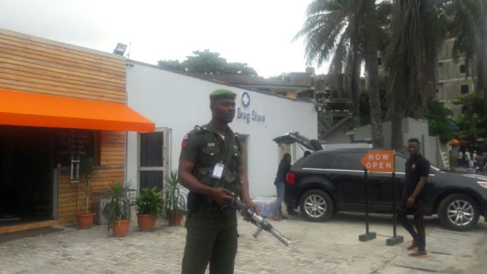 Armed policemen guard the Nuli Juice shop in Ikoyi, Lagos before it was demolished with the government giving the owner only a 24 hour notice