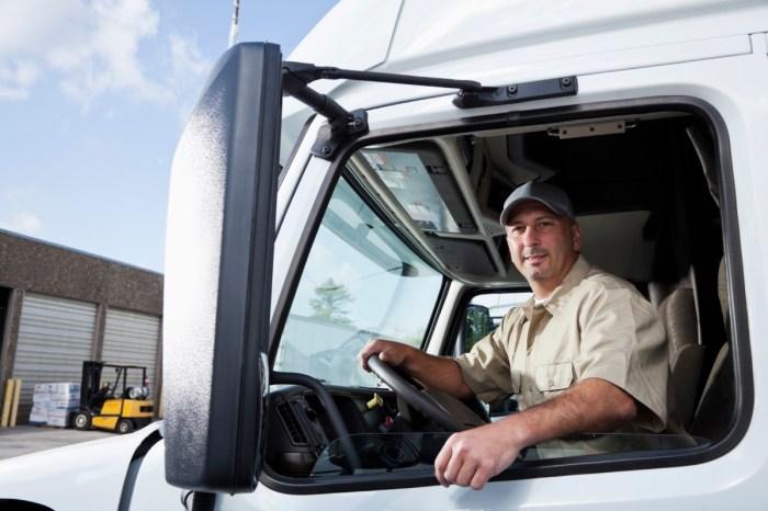 Truck driver (30s) sitting in cab of semi-truck. professions stamina