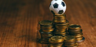 Soccer bet concept with small football on top of coin stack, making money by predicting sport results. betting