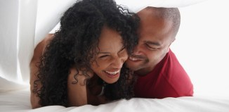 Smiling Black couple underneath sheet