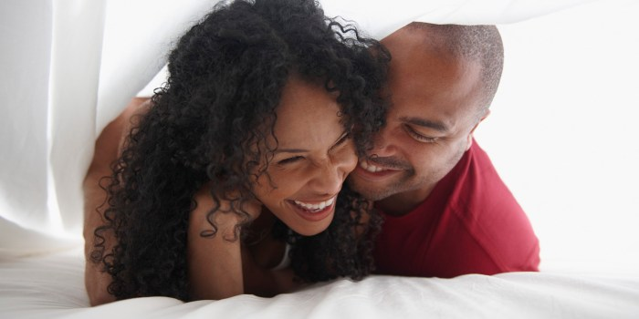Smiling Black couple underneath sheet