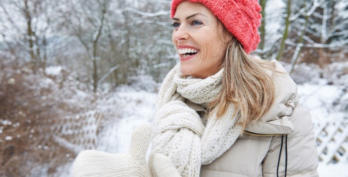 Happy smiling woman standing in winter clothing outdoors in the snow Happy smiling woman standing in winter clothing outdoors in the snow